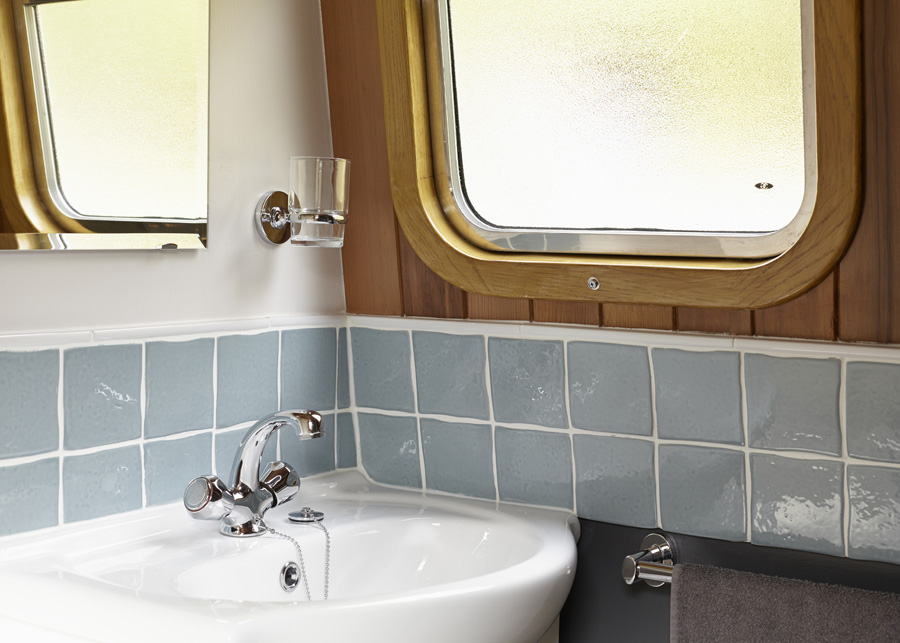The narrowboat's bathroom is modern and has a sink and shower and also storage areas and places to hang clothes and towels.